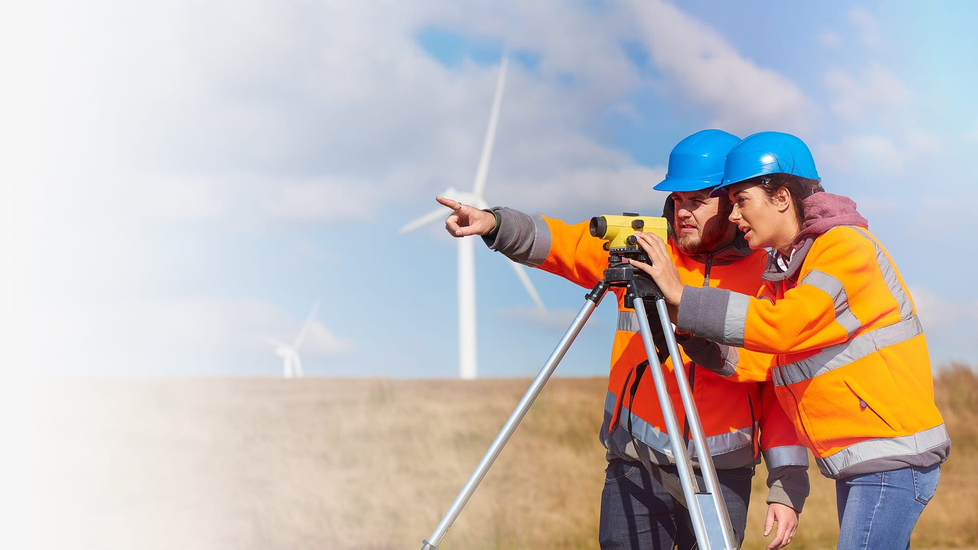 Two utility workers from an oil and gas management company surveying a location for a new field of wind turbines.