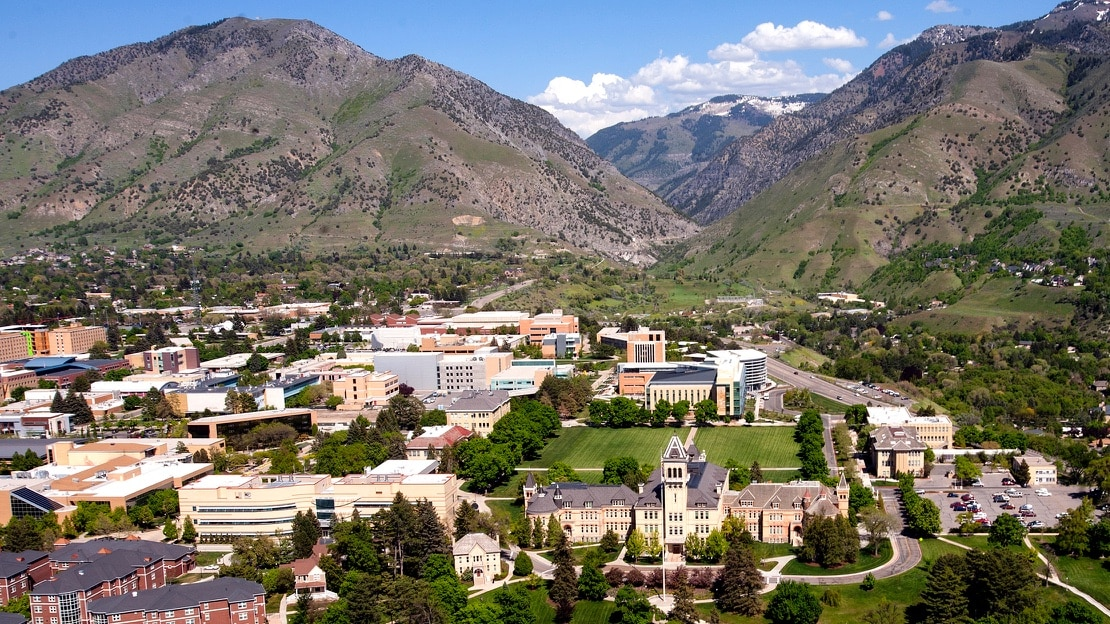 An aerial view of the Utah State University campus nestled between some mountains on a sunny, spring day